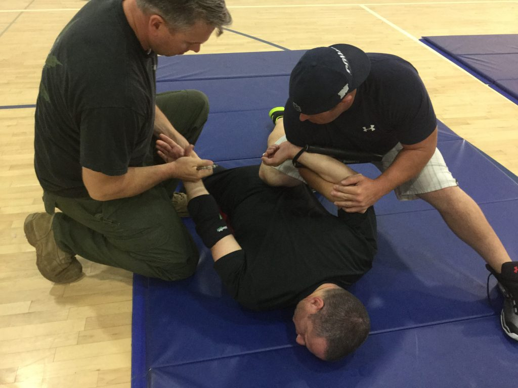 Man face down on the mat after being restrained.