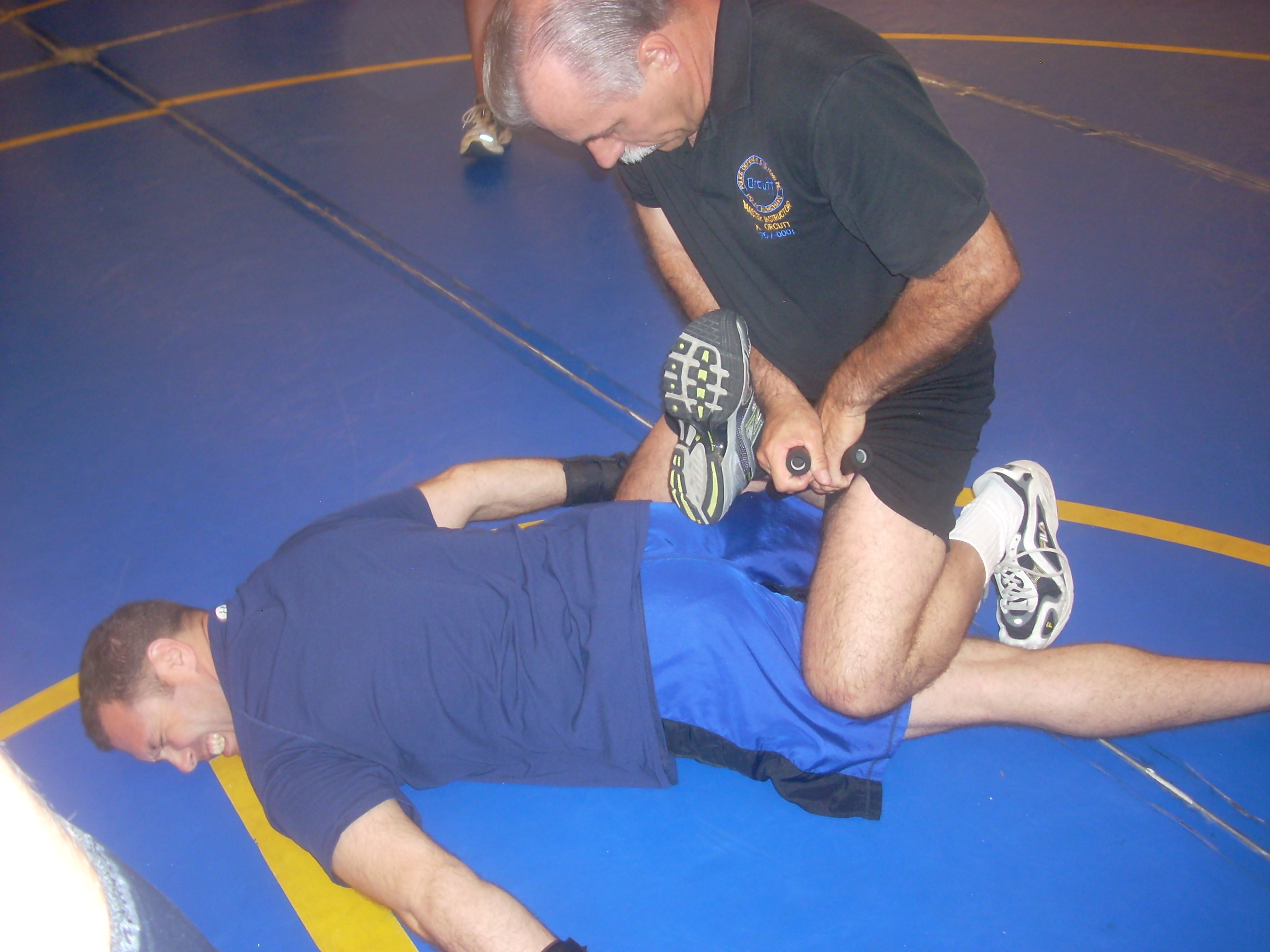 Man in blue being restrained by the ankle.
