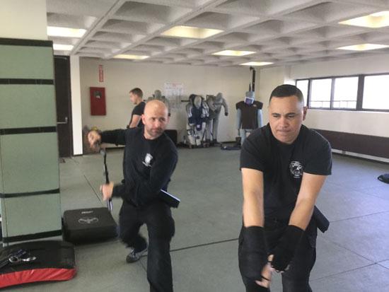 Men practicing restraint tactics in gym.