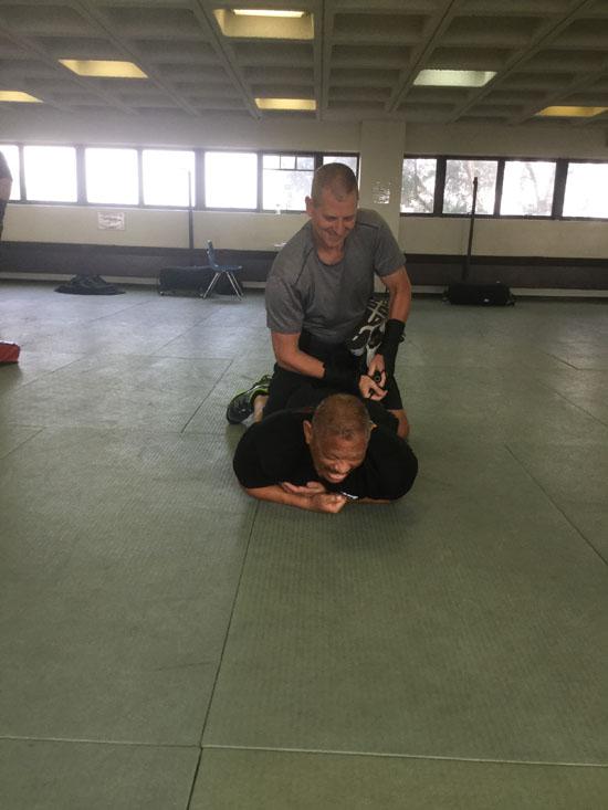 Man in grey practicing OPN restraint techniques.