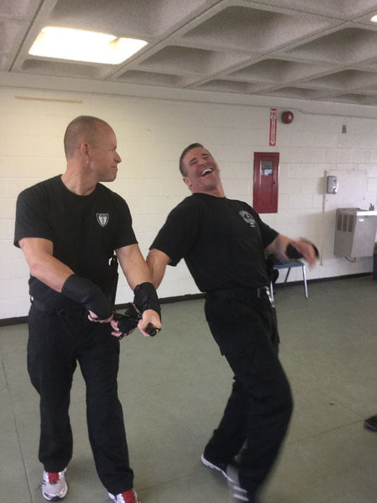Men in black t-shirts practicing OPN restraint techniques.