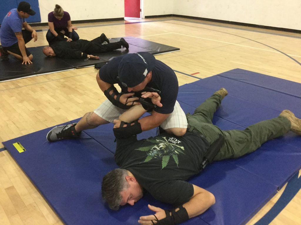 Man in green pants being restrained.