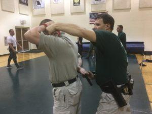 Men in black t-shirts practicing restraint tactics.